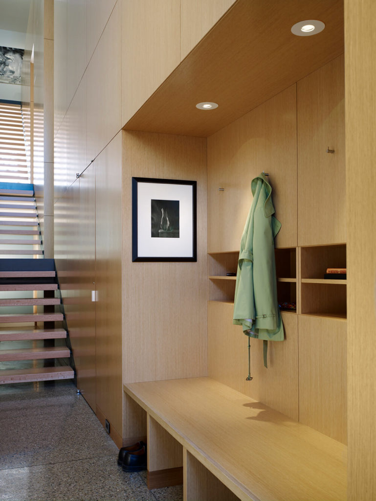 With open risers, the staircase remains an open visual space, full of light. At the bottom, the wood panel walls form into a friendly bench and storage space, perfect for an entryway.