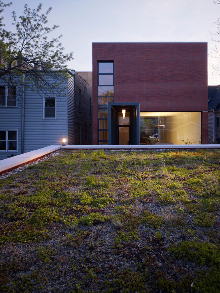 A view over the garage structure at dusk reveals its innovative green roof construction, perfectly highlighting the way this highly progressive home was built with an eye toward sustainability and efficiency.