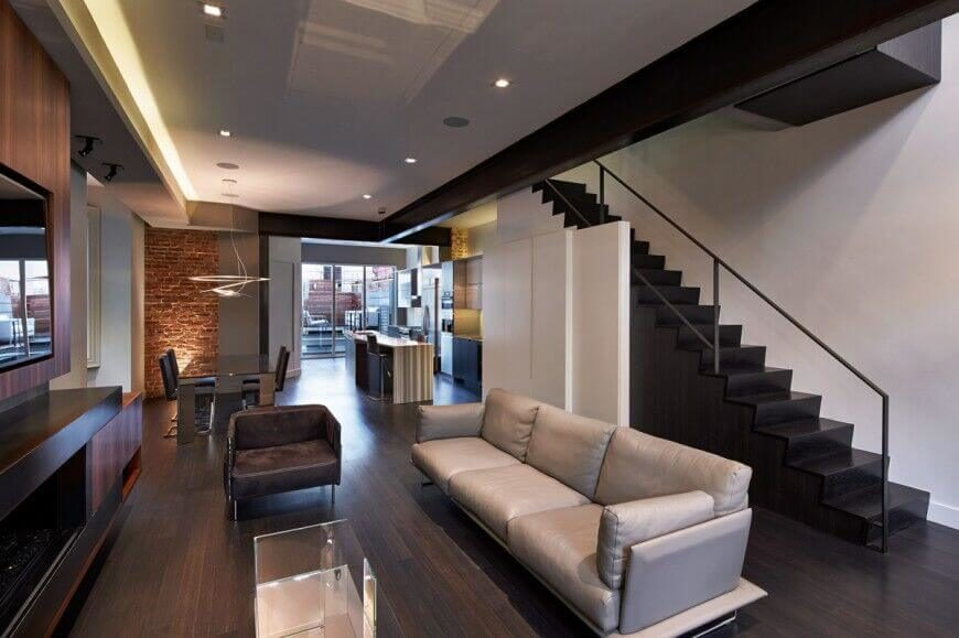 This modern home features an open-concept living space with accents of wood and of brick. The kitchen and living room are separated only by open floor, with no barriers.