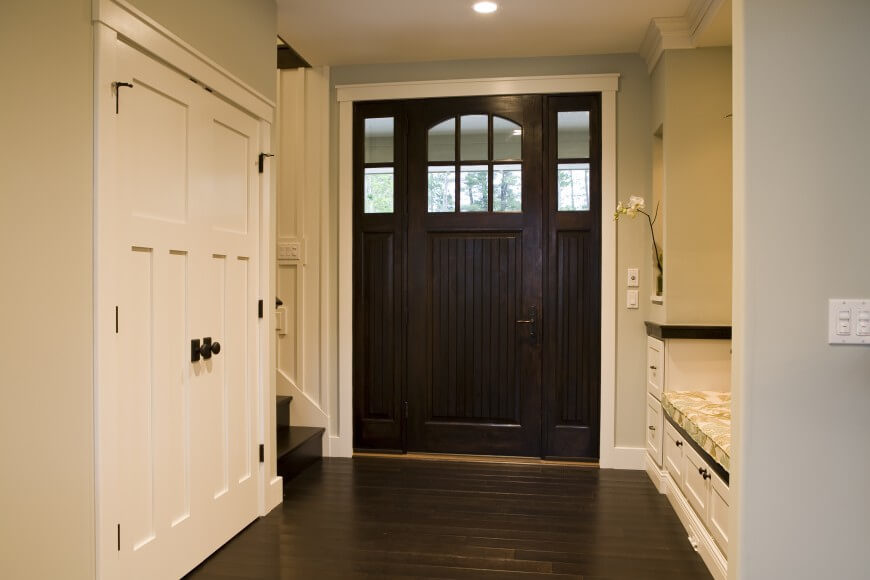 This lovely foyer utilizes dark wood to ground the small space. A built-in bench and shelf area is a smart use of functional space in such a small area.