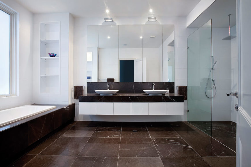 The primary bathroom spreads over an expanse of dark marble flooring, with a glass enclosed walk-in shower at right and large soaking tub beneath the window at left. The floating double vanity features white cabinetry and a marble surface supporting a pair of white vessel sinks.