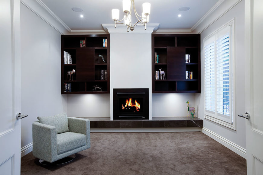 Here's a more cozy room in the home, with traditional sized window, centered on a bespoke gas fireplace. A pair of dark wood shelving sets flank the chimney, while a singular swivel-mounted club chair stands on the brown carpet.