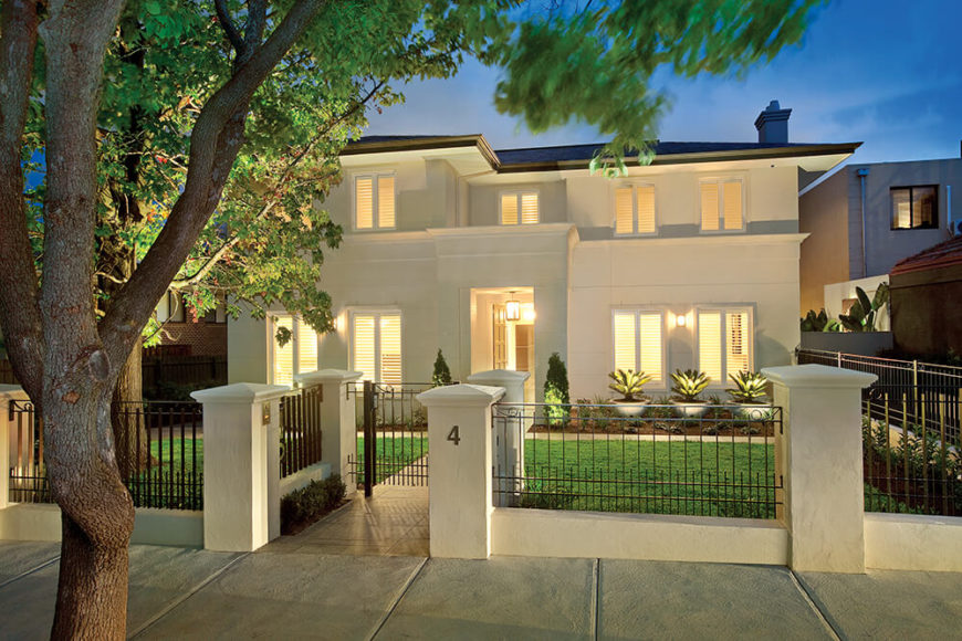 While the backyard and integrated pool area is the clear showcase of the exterior, the front of the home competes for attention with a bespoke white-clad facade, tightly manicured yard, and surrounding white and wrought iron gate.