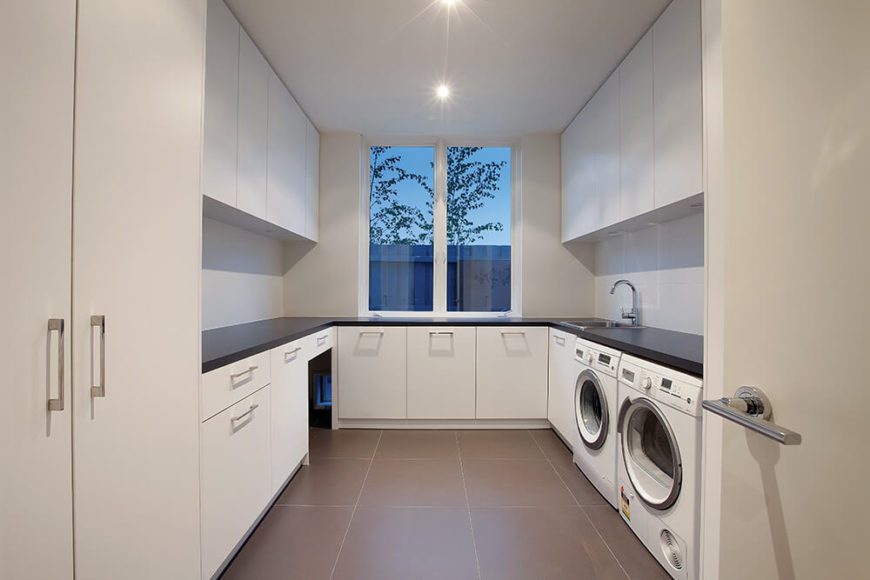 The home contains a fully decked out laundry room, replete with white cabinetry and black countertops. Large format brown tile flooring acts in smart contrast, adding warmth and a connection to the tone of the hardwood elsewhere in the home.