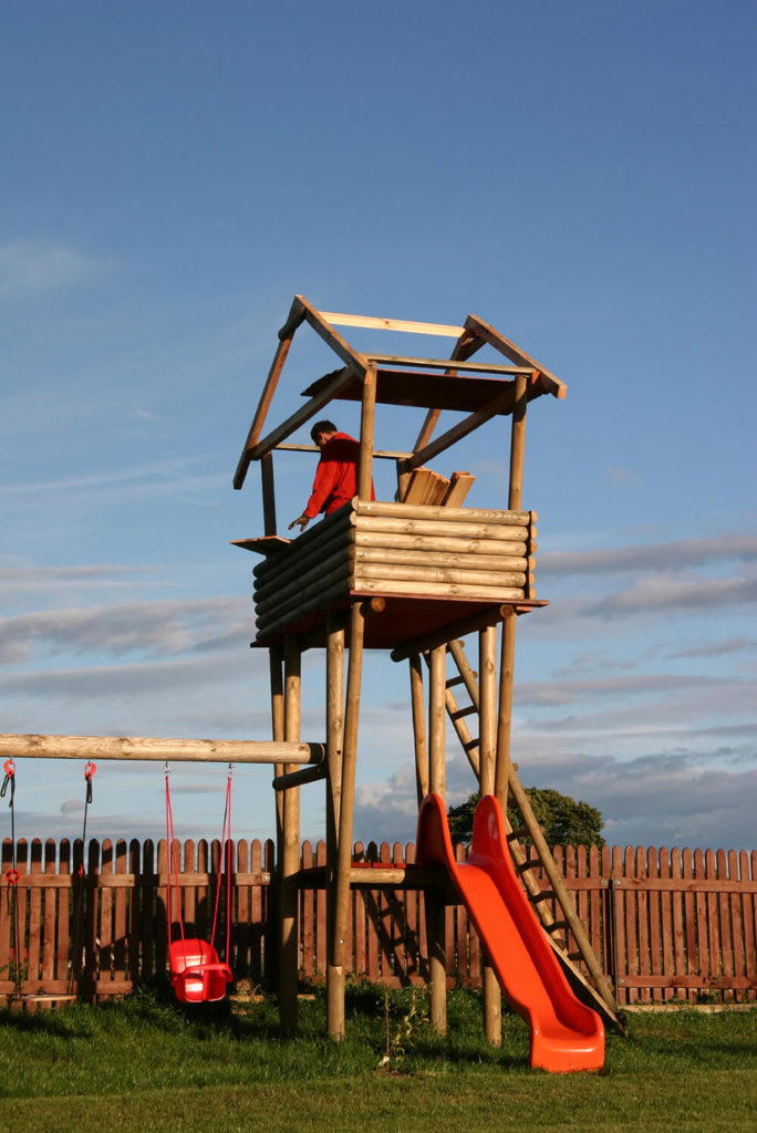 This playset, when finished, will have a log-cabin style atmosphere, a large, sturdy swingset, and a slide, in addition to the tall lookout tower.