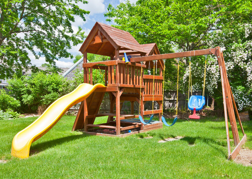 A sandbox sits below the fort section of this large backyard playset. This set also includes a spyglass.