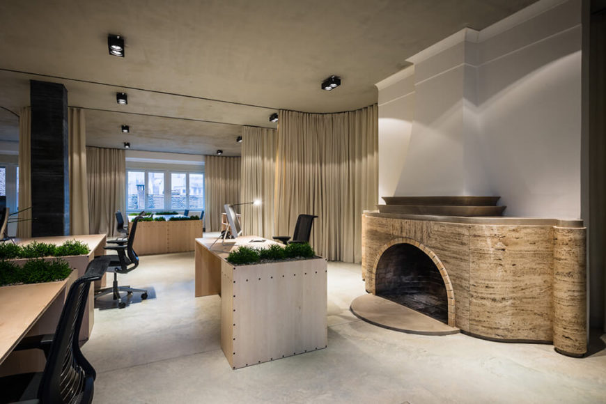One of the more elegant flourishes in this office is a large marble fireplace, curving around a central wall at the end of the space. The material stands in contrast with the rest of the layout, but the shapely design echoes that of the dividing curtains.