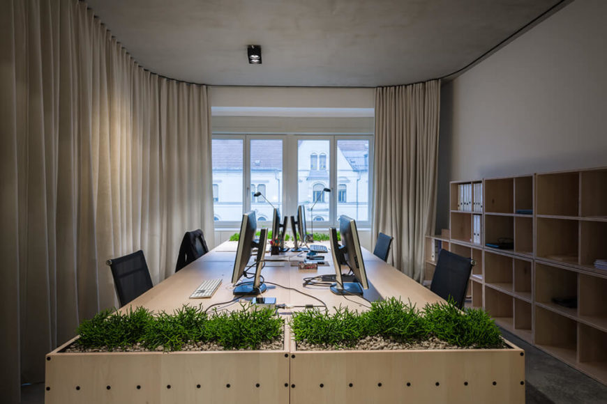 Now with a pair of curtains enclosing, it's become a discrete office. The cube-based storage at right and the ever-present desktop gardens enhance both the utility and aesthetics of the room.