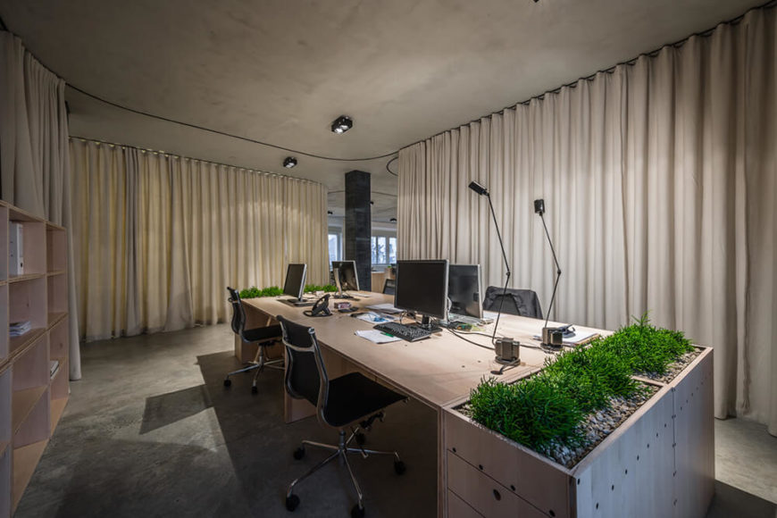"""As one curtain parts, we see another distinct space drawn by curtains across the newly made """"hall."""" This opens the corner office up to the larger common area but not completely."""