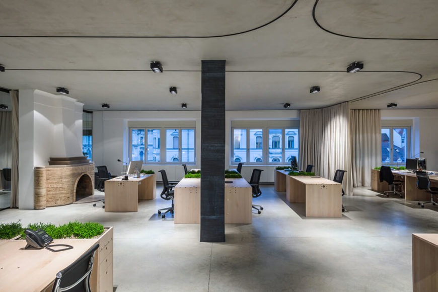Pulling back to a wide angle, we see a grand sweep of the entire space with the curtains fully opened. Natural light pours in, enhanced by the bright wood of the desks and white walls, illuminating the broad open space.