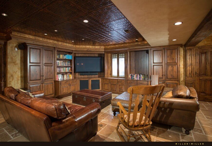 This cozy family room looks perfect for a night in with a movie. Comfy leather furniture matches the rich wood decor while the pressed ceiling tiles add textured interest to the space.