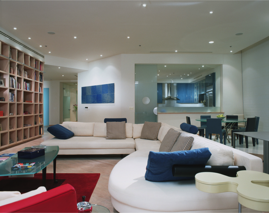 This modern family room creates a calming space with different shades of soothing blue. Inclusions of bright red add pops of interest through the room while lots of glass creates a different in texture.