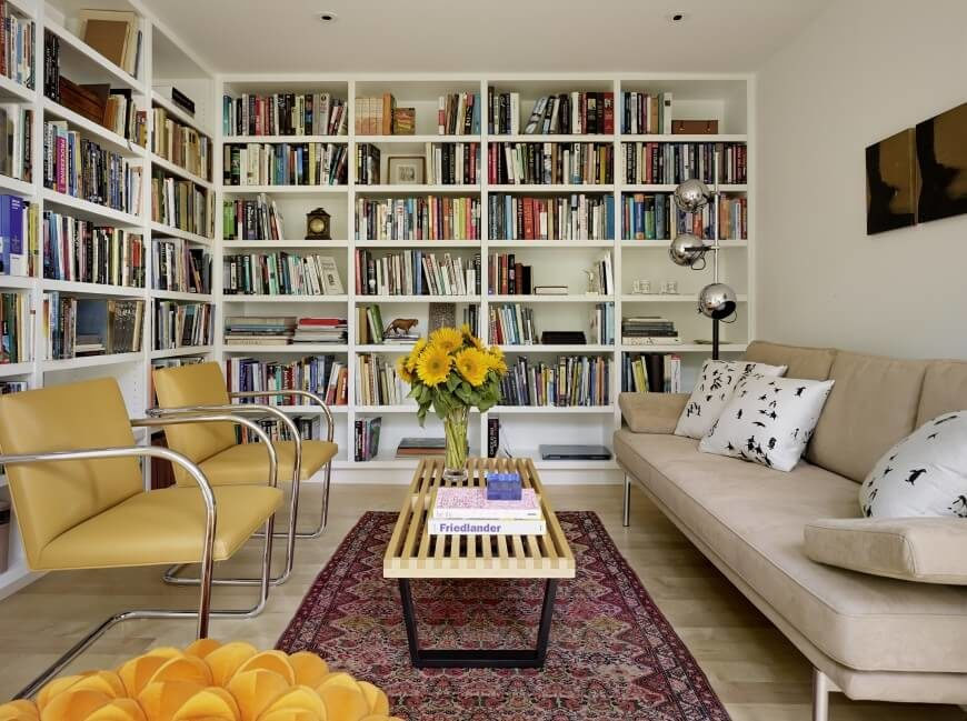 The other end of the room from above, floor to ceiling bookshelves create storage and interest in the white walls of this narrow space. Neutral and faded tones allow the colors of the books to pop out and supply most of the color in the room.