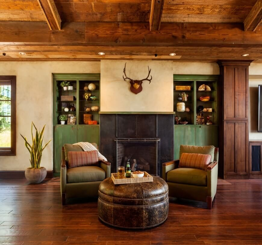 Green accents in this room complement the warm flooring and the worn leather ottoman. Metal paneling around the fireplace stands out from the rest of the room with its industrial style.