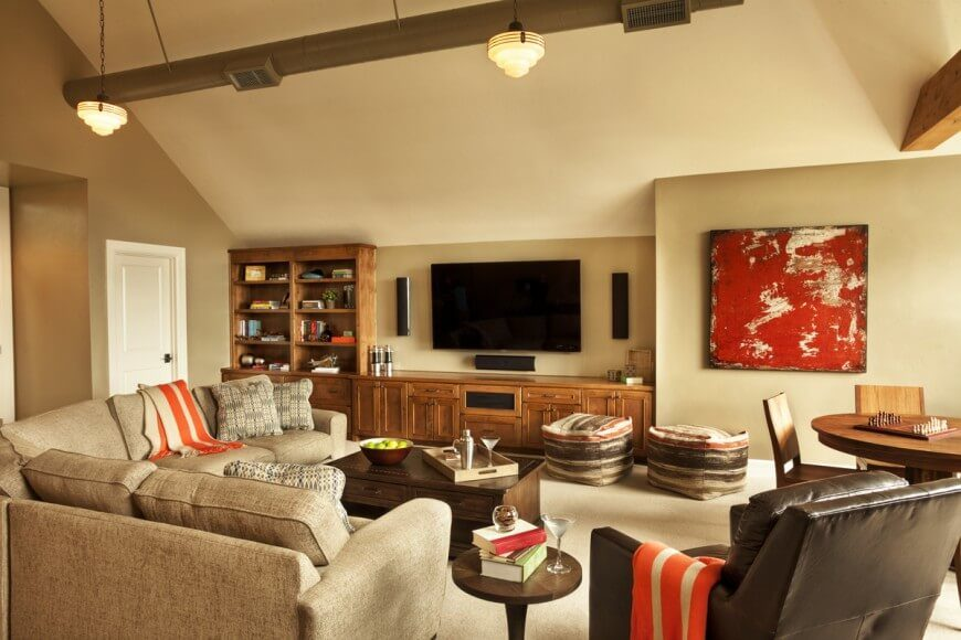 Bright orange accents complement the warm but neutral palette of this charming family room. Rich browns next to subtle tans create a wonderful juxtaposition of colors and furniture pieces.