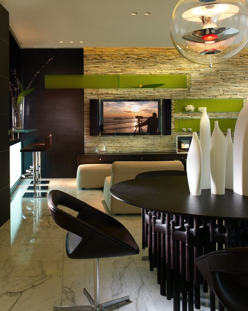 A stacked stone accent wall creates a lot of visual interest in this room. When combined with shelving the color of new leaves it almost looks like tree bark or wood instead of stone. Dark wood accents help with area to pop a bit more against its backdrop while the bright white bottles utilize organic curves to both complement and contrast the room.