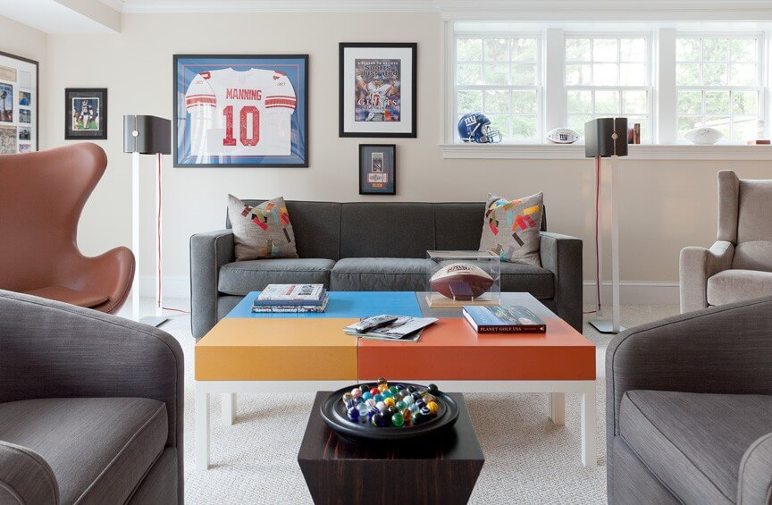 This fun room utilizes bright color blocks and accents to contrast the light tones and muted grays of the decor. Including multiple styles of furniture also helps to create interest without having to crowd the room with decor.