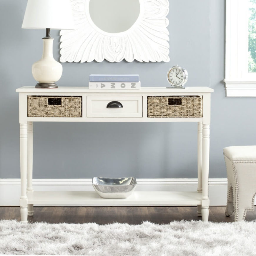 This long white console table has decorative table legs along with a single wooden drawer and two wicker drawers on either side. The wicker adds texture and rustic charm to the pristine white piece.
