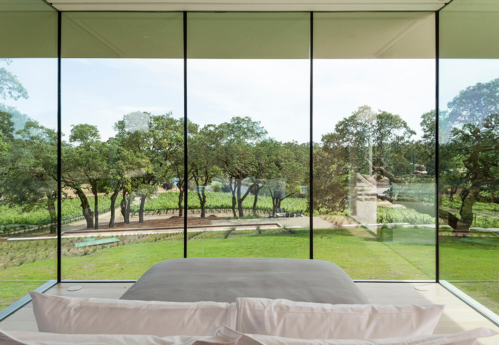 Primary bedroom with shiplap floor surrounded with paneled glass walls letting you enjoy a serene ambiance of the magnificent expansive yard.