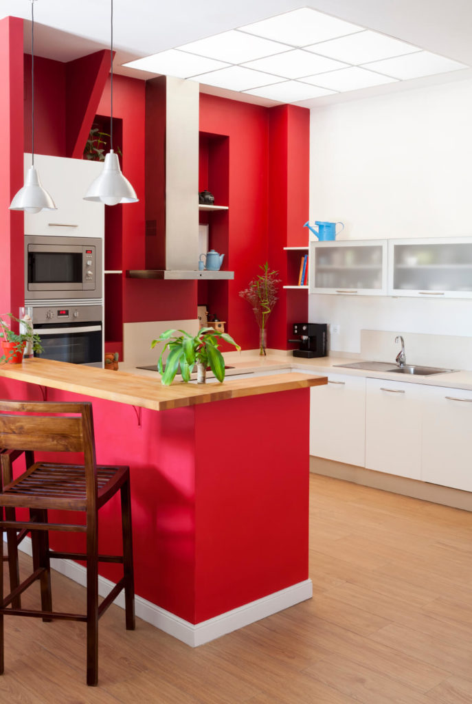 The obvious centerpiece to this kitchen's style is the bold red paint adorning the walls, in direct contrast with white cabinetry and natural hardwood flooring. The raised wood countertop in the foreground acts as a perfect dining space while defining the edge of the kitchen itself. Contemporary stainless steel appliances enhance the modern look.