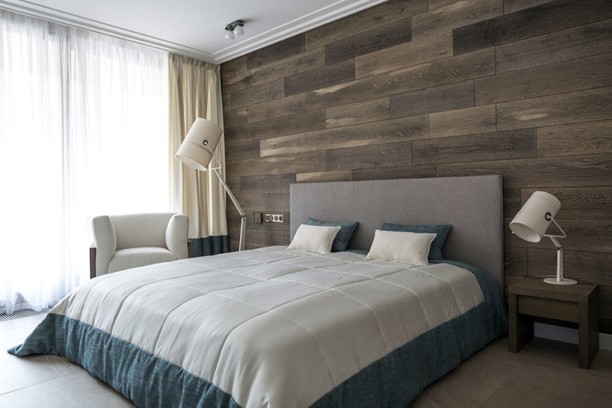 As we move into the primary bathroom, we see another wooden plank accent wall, which contrasts with the gray fabric headboard. A matching floor lamp sits across the bed from the lamp on the nightstand.