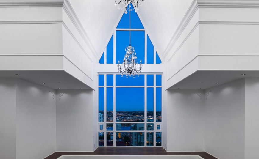 The third floor vaulted ceiling that started in the library on the first floor. This small balcony area opens into the primary bedroom while the expansive window gives a stunning view of the city and allows for plenty of bright light during the day.