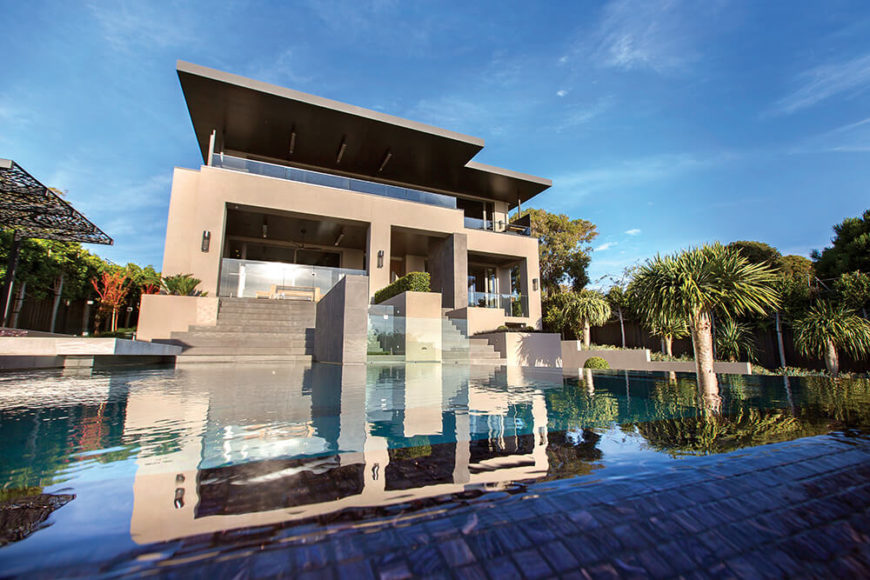 The pool ends in a sloped wet infinity edge, spilling downward organically for a perfectly clean surface appearance. Steps from the patio lead directly down to the water feature.
