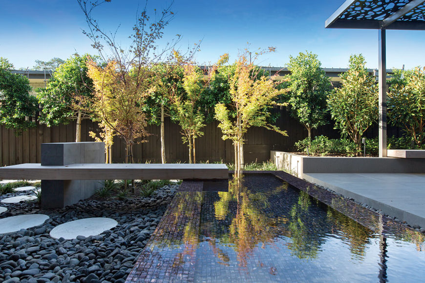 Over the reflecting pool, we see the beautifully interlocking pathways for movement in the yard, including the bespoke circular stone path and built-in bench at left.