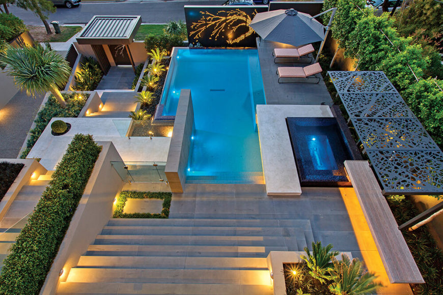 When viewed from above, we can fully appreciate the geometric complexity of the landscape, shaping organic and manmade elements into a beautifully relaxing mosaic. The pool stands central, its blue glow contrasting with the greenery and concrete surrounding.