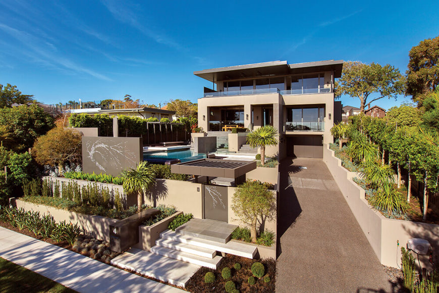 This modern home features a sprawling landscape design with integrated pool.