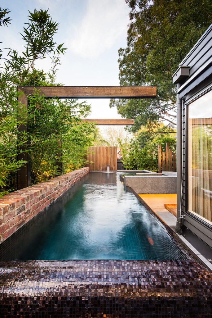 The pool wraps around the home and deck structure, a lengthy, pristine water feature with wet mosaic tile edges.
