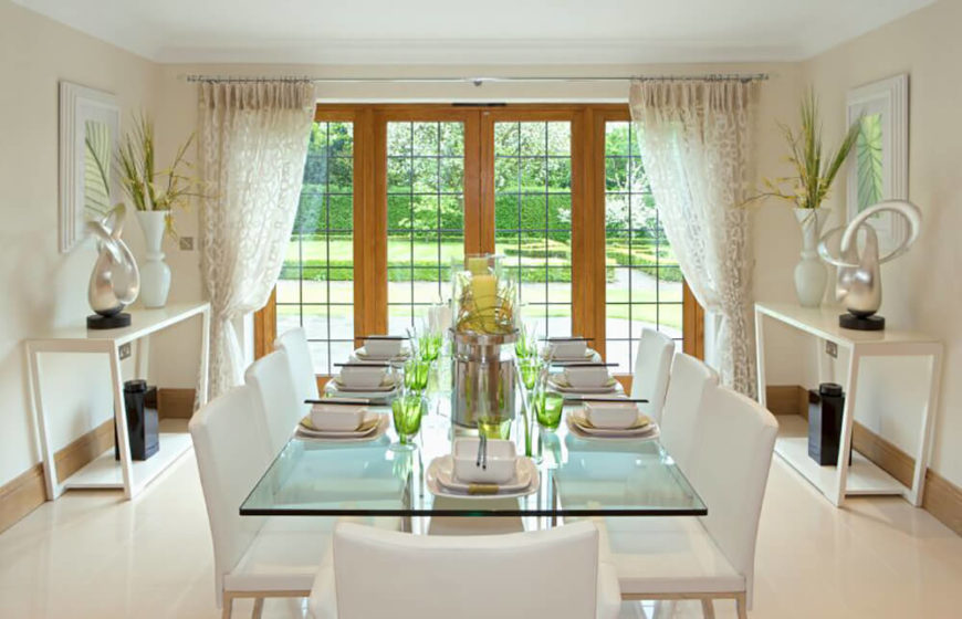 Elegant white dining room with white upholstered chairs and glass table.