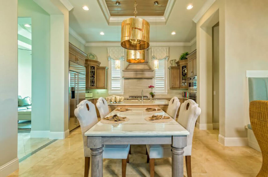 This modern open-plan home features a dining room in a larger space including a kitchen. The marble topped dining table stands over beige marble flooring, flanked by a set of ornate, white upholstered chairs.