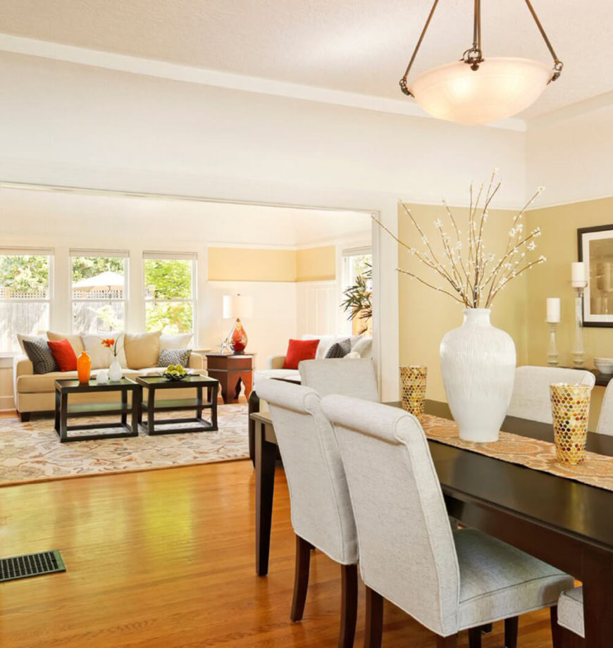Bright soft yellow walls and warm hardwood flooring are contrasted in this dining room by a deeply stained wood dining table. The chairs feature roll-top backs and soft grey upholstery.