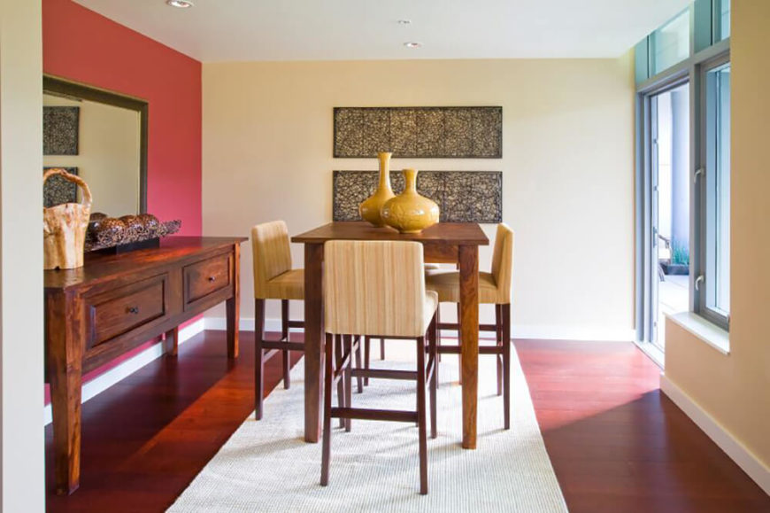 This dining room features a sharp contrast between rich hardwood flooring, off-white walls, and a bold red feature wall, at left. The high-top natural wood dining table is surrounded by tall chairs with light striped fabric upholstery.