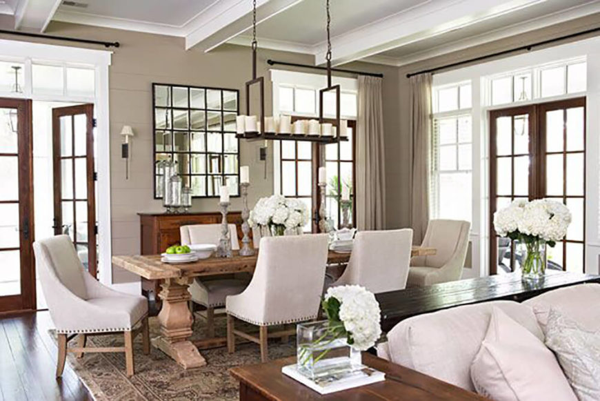 Traditional elegance mixes with a hint of rustic charm in this large dining room set into an open-plan space. Sunlight pours through glass doors into the area, centered on a large natural wood table and nailhead-trimmed Parson chairs.
