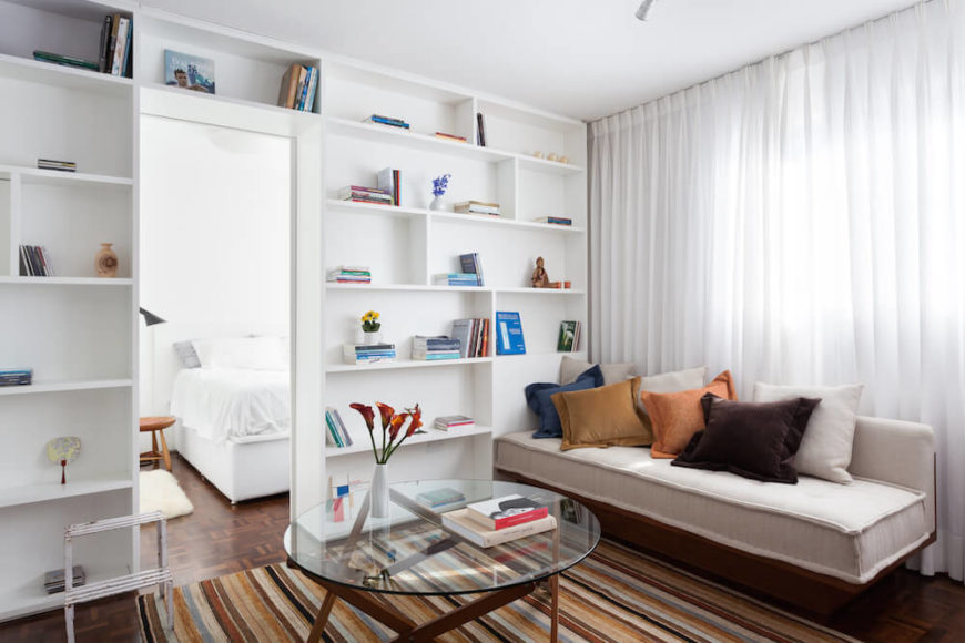 Here, we have a photo of the main part of the house. The living area has a beautiful sheer white curtain that lining the wall and floor-to-ceiling shelving. The hues in the carpet complement the colors of the pillows on the couch for a unified scheme.
