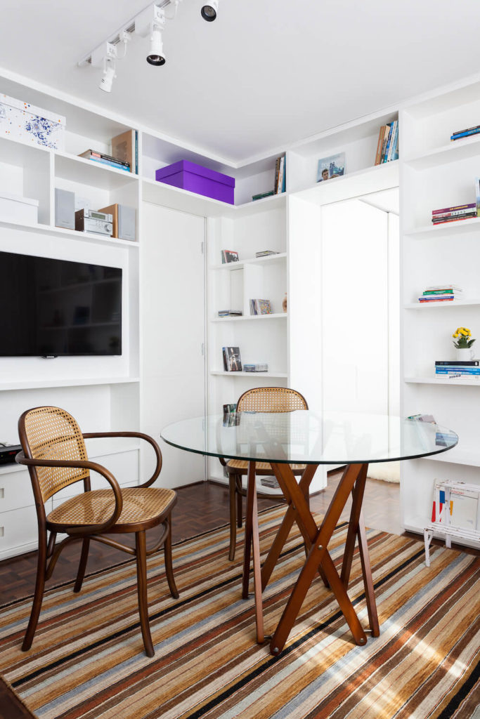 Chairs can be pulled around the table in the living room when it's time for dining. The dining area and living area combine smoothly to save space, and also add more seating to the communal area.