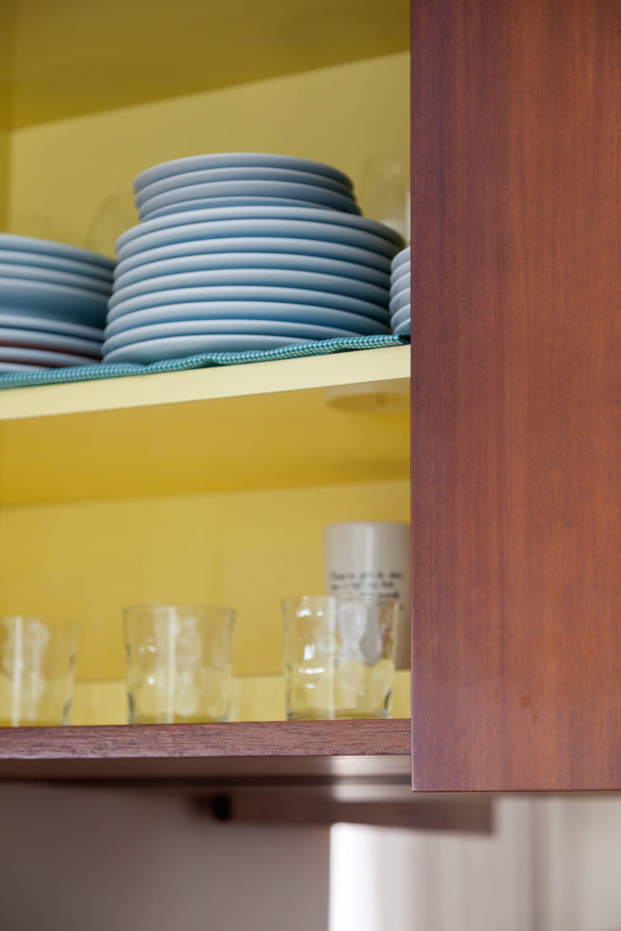 Here we can see one of the upper cabinets in the kitchen. A burst of bright canary yellow is hidden inside of the cabinet for a surprise splash of color.