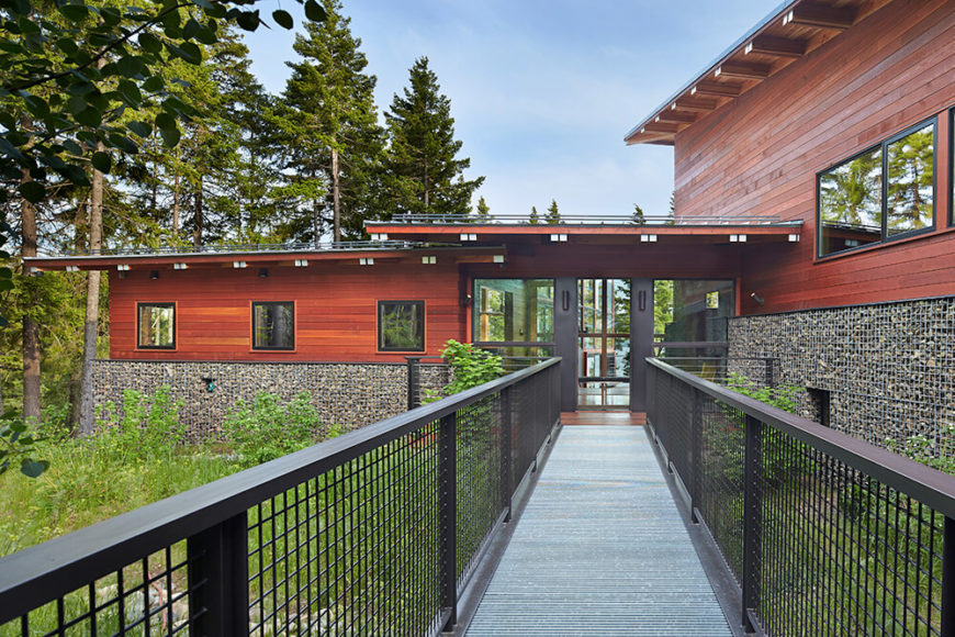 This captivating glass entrance allows you to see straight though the house and out to the breathtaking view of the lake beyond. This is an excellent example of blurring the lines between the interior and nature. The walkway allows access to the house without disturbing the dry stream or the plant life around the exterior.