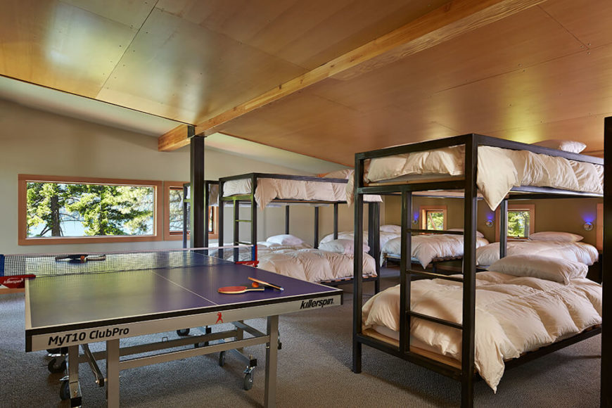 This large bedroom is reminiscent of a camp bunk house while still maintaining the level of comfortable luxury throughout the rest of the house. The ping pong table offers some additional recreational fun.