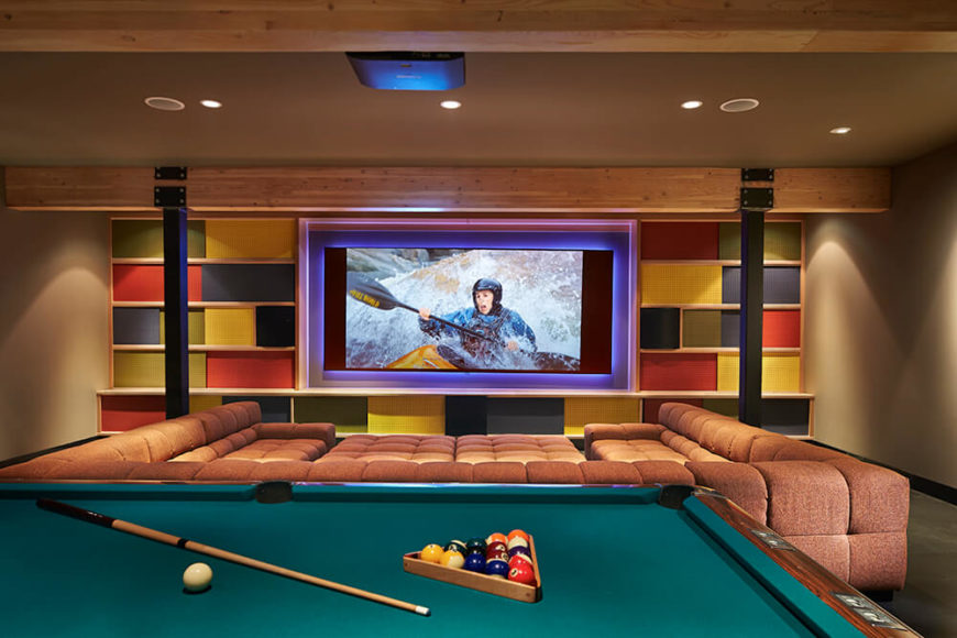 The rec room is a nice hideaway to relax and unwind. The built-in screen for the ceiling-mounted projector is surrounded by fun, colorful wall decor. The large couch offers plenty of room for family and guests to enjoy a movie while the billiards table in the foreground provides a different kind of fun.