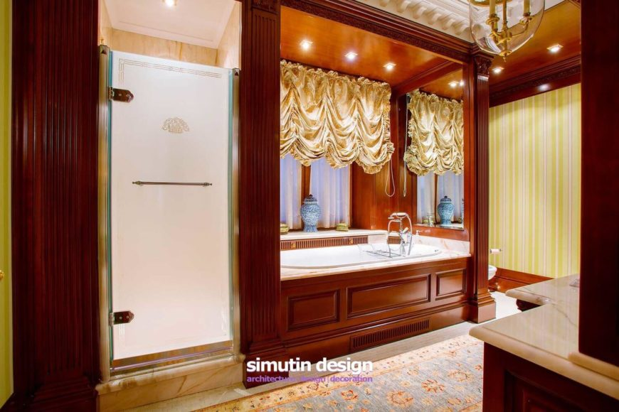 The primary bathroom features a steam shower encased in marble, marble countertops and a soaking tub enclosure, and silken, ruched curtains.
