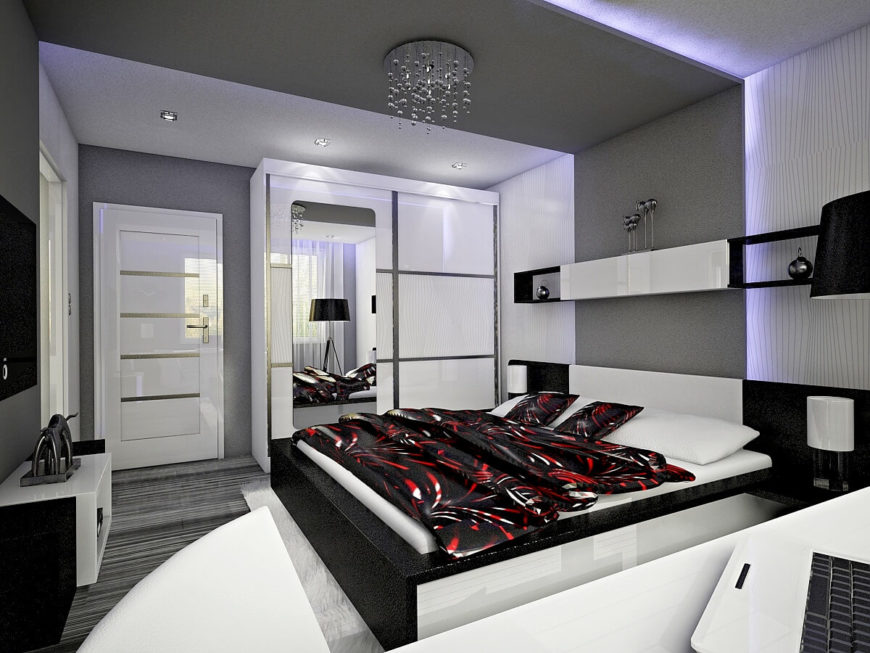 Upon entry to the primary bedroom suite, we see the enormous platform bed and a plethora of minimalist storage options. Another full length mirror is hung on one of the wardrobe doors. A modern, yet glamorous crystal chandelier hangs directly above the bed.