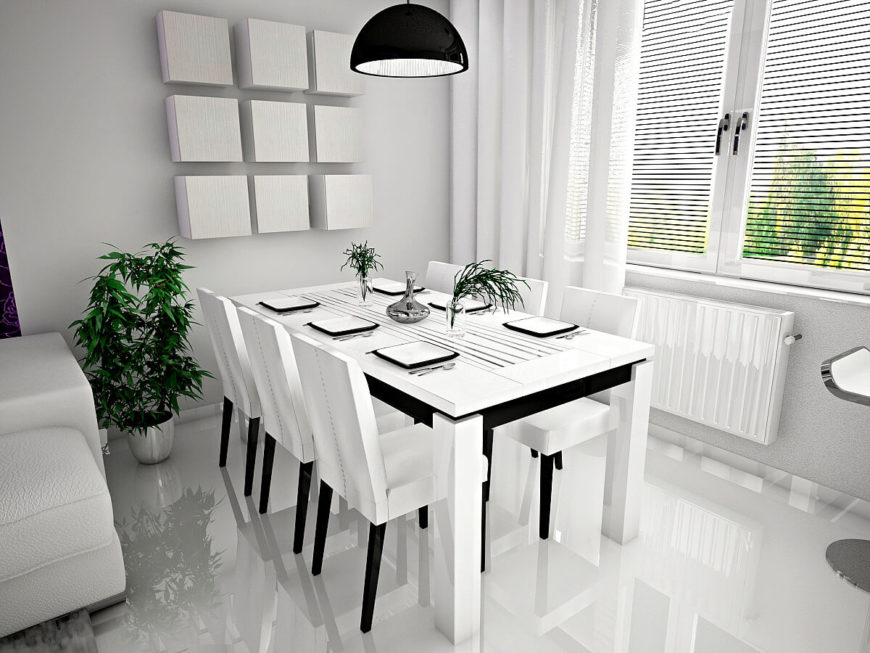 As we move into the main living areas of the home, we enter an open-concept space, which includes this lovely dining room. Like the foyer, this area is monochromatic, with several houseplants in metallic planters. The windows consist of massive shutters that can easily be opened to let in light and air.