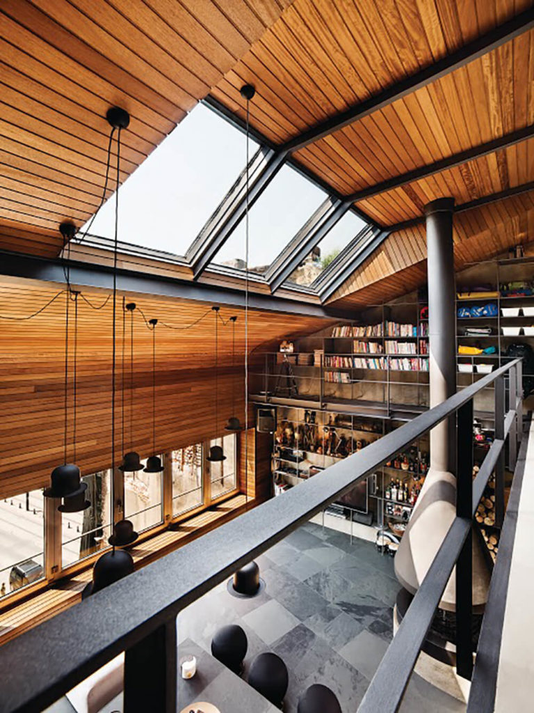 "Anchored at the center of the iroko wood paneling that stretches from the lower wall to the peak of the ceiling, the set of massive skylights help with the ""balcony"" feel of the mezzanine, with abundant sunlight spilling directly down."