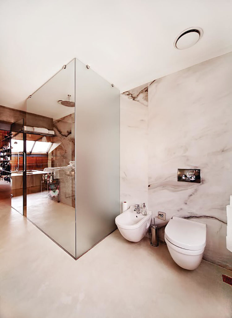 The bathroom sports a glass enclosed shower and a broad marble wall, making a novel combination of high tech and traditional materials.