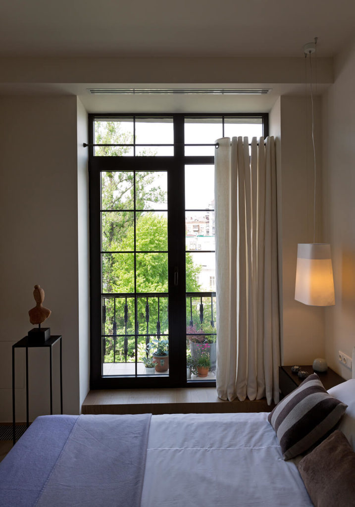 With modern doors framed in black, the balcony is updated and fully accessible. with the bed providing the lone appearance of color in the room, the remainder is unified in neutral tones.