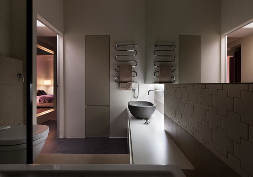 The bathroom is granted an ultra-modern touch via stone vessel sink and wall-mounted faucet, as well as chromed drying rack mounted on the wall above. The flooring here is dark large format tile.