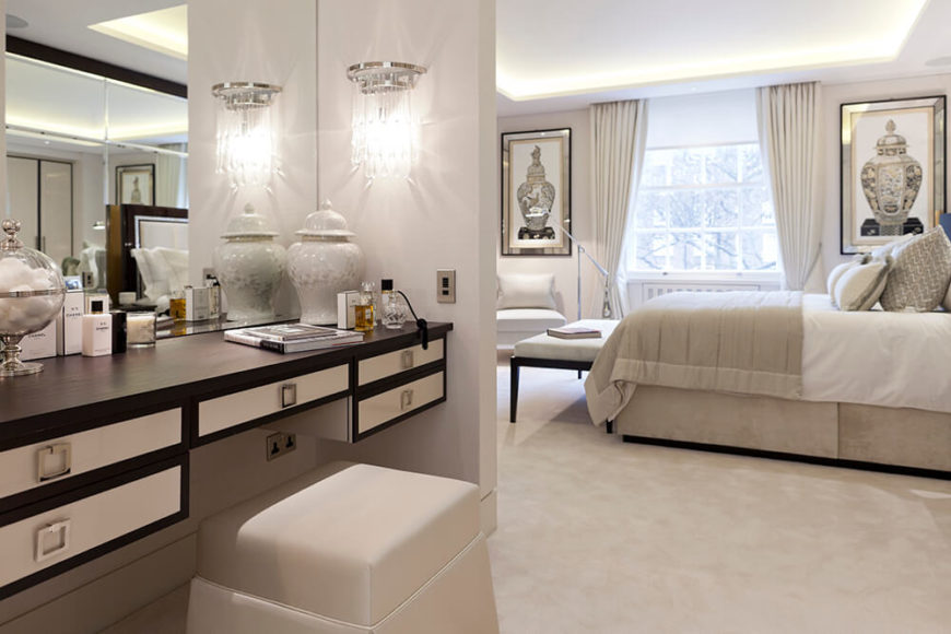 The bedroom en suite includes this large makeup desk, with a skirted ottoman for seating. Artwork in the bedroom is mirror-framed, flanking a large window below recessed lighting in the ceiling.
